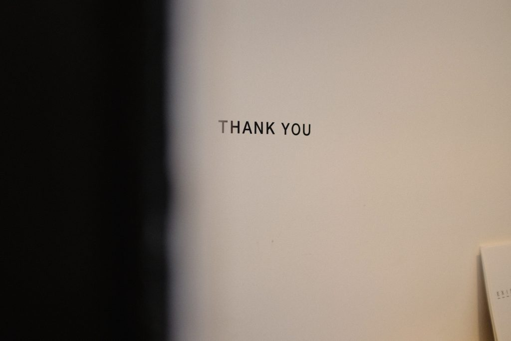 a thank you words written on typewriter letters on the white wall in a dim room